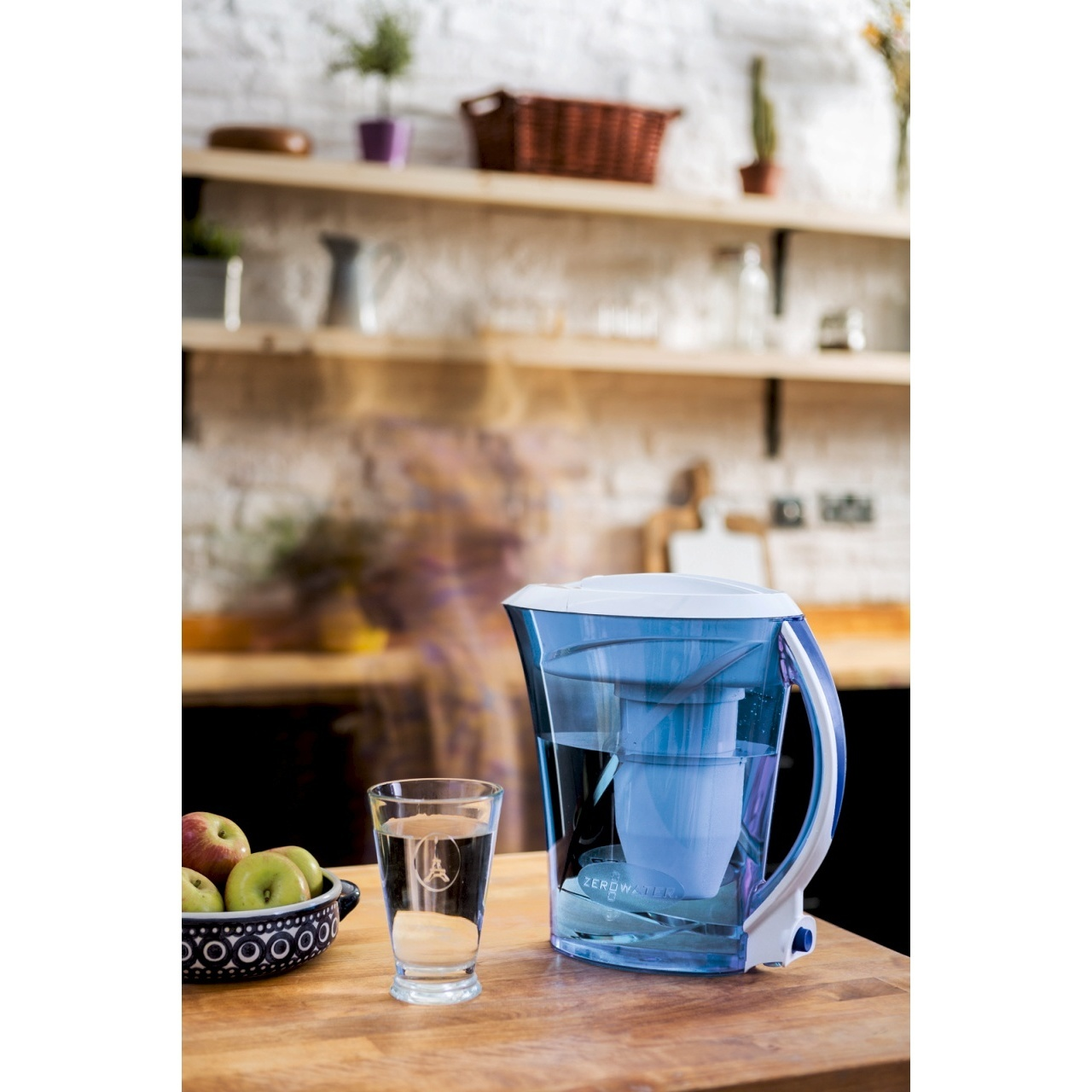 Light blue water filter jug on a table with glass kitchen background