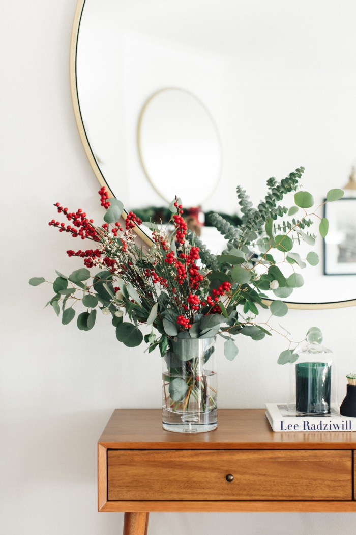 Christmas trends flower decor green and red arrangement in a glass vase in front of a mirror