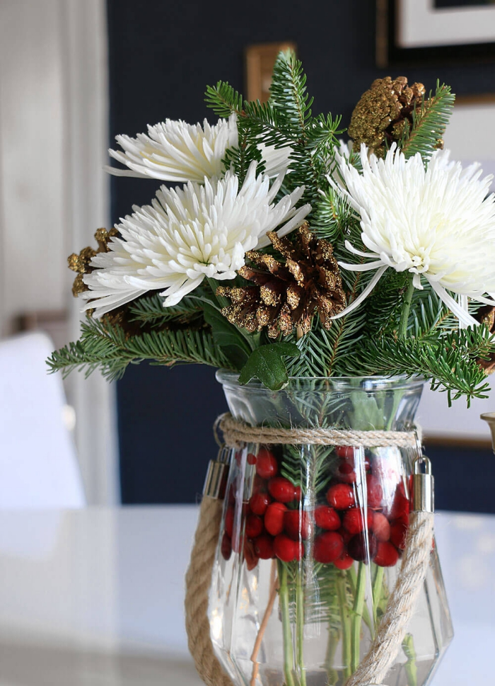 Close up christmas flower arrangement with gold spray painted pinecones white flowers green branches and berries