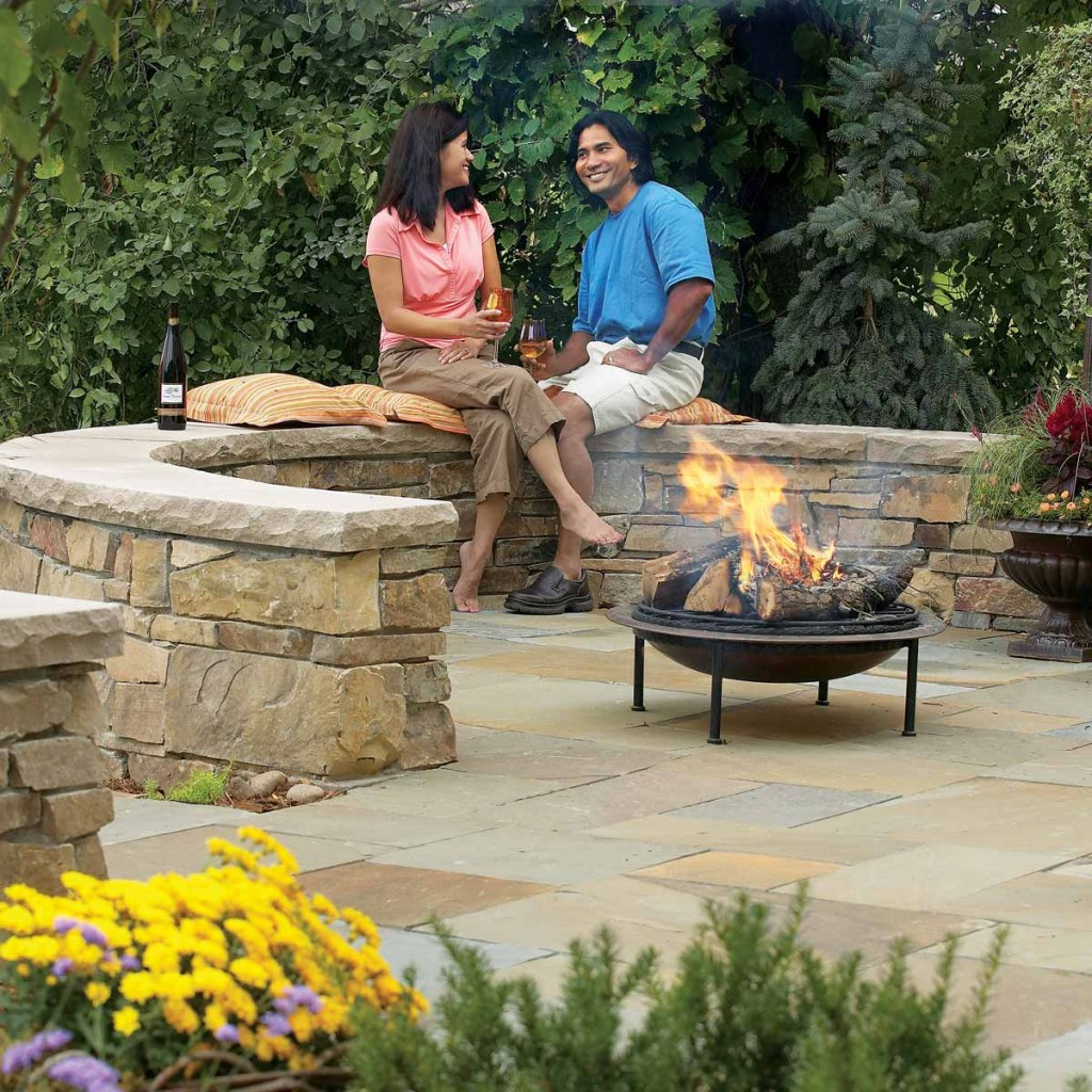 Patio stone walls couple enjoying wine fire pit