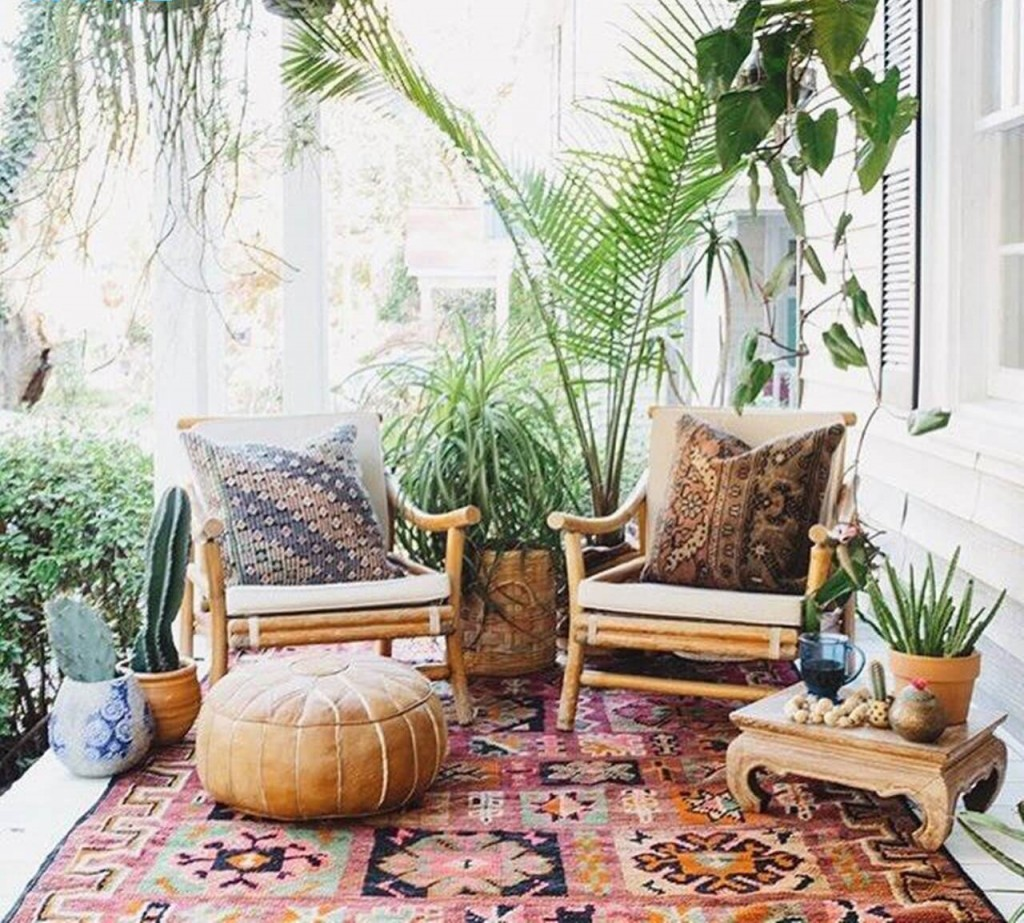 Boho style small patio with ottoman small table cacti greenery two chairs