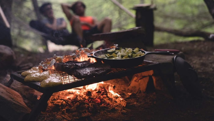 two people sitting in the background grilled dinner fire camping
