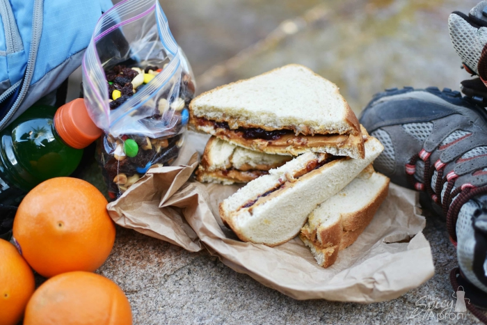 camping food peanut butter sandwich with oranges bottle and snack