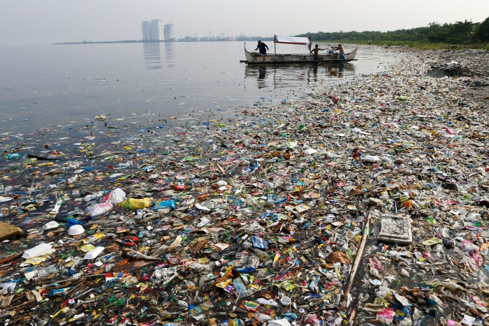 Plastic beach litter worldwide sea with a lot of litter boat with people tall buildings