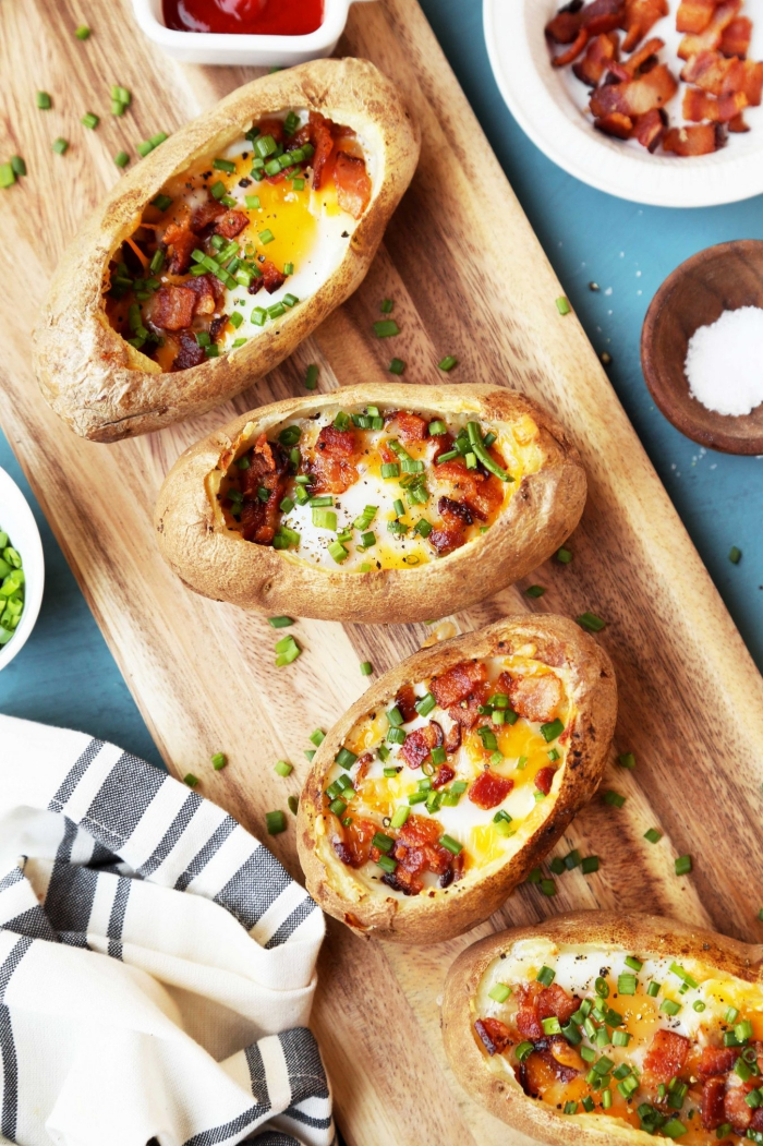 Potato Boats on a wooden board with salt bacon and chopped onion