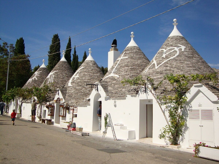 street with trullo houses people on the street white houses trulli Italy Puglia