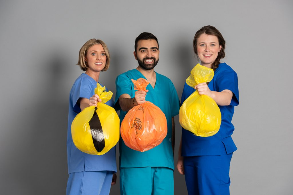Three doctors haveing medical waste in their hands