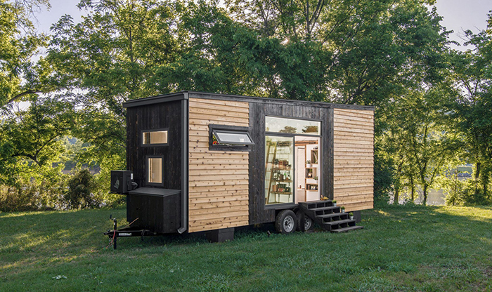 Modern wooden tiny house on wheels on a green lawn trees