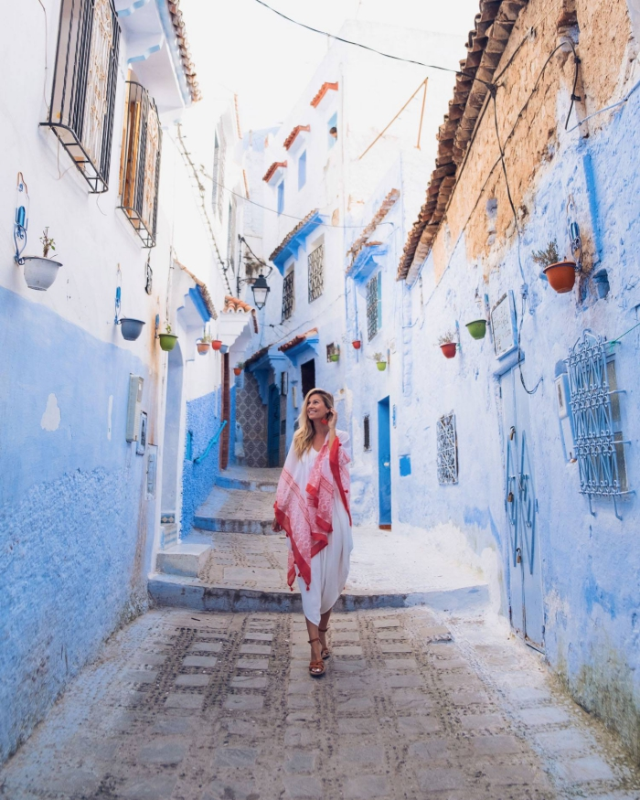 woman with a red scarf in a beautiful setting white and blue brick houses