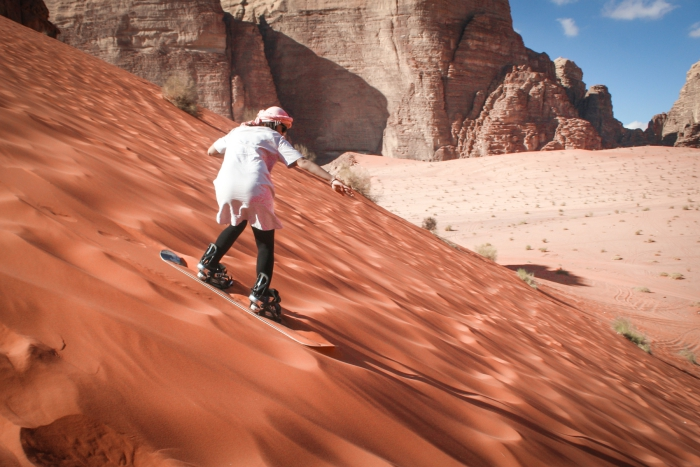 Man with shemagh sliding down a dune in the desert