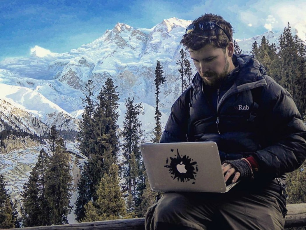 man with his laptop in the mountains software engineer snowy peaks