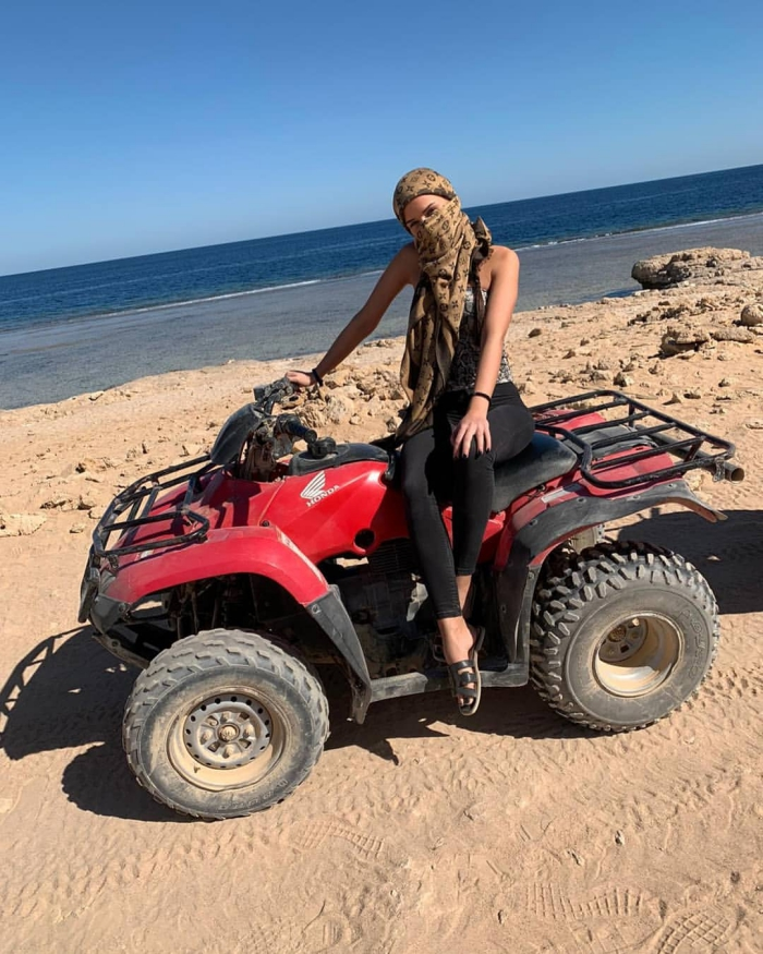 Travel with shemagh woman on ATV with a shemagh around her head beach red atv