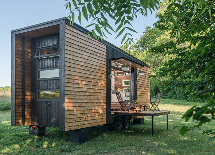 Best Cozy Tiny Homes wooden home on wheels with a small balcony in a field