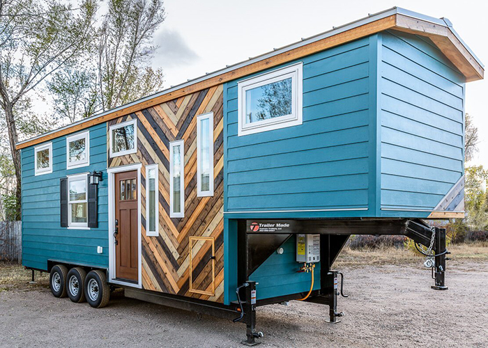 Blue home on wheels with many windows and wooden part