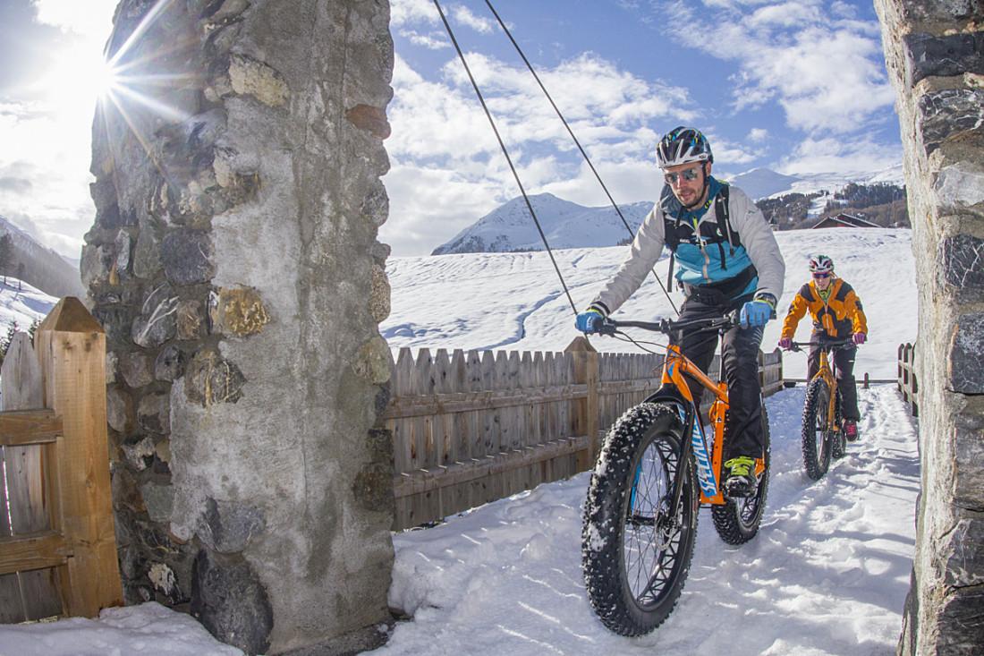 Livigno winter biking bikers two men biking winter landscape