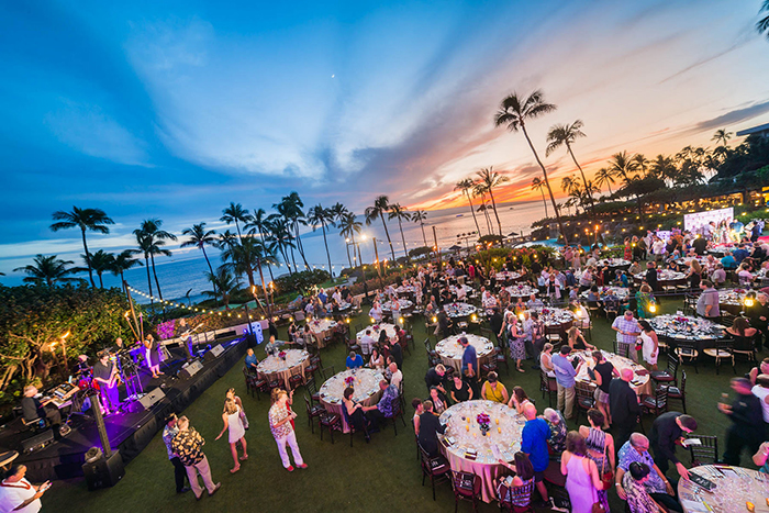 Food and Wine Festival Hawaii outdoor stage people dining tables on a lane palm trees sunset