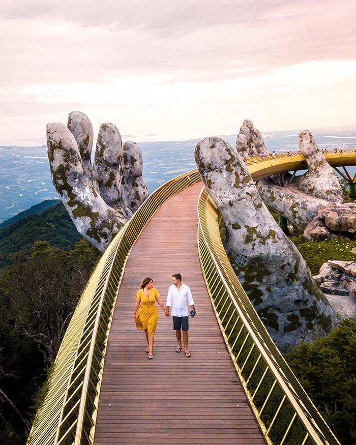 Couple holding hands Golden Bridge Vietnam Hands in the background
