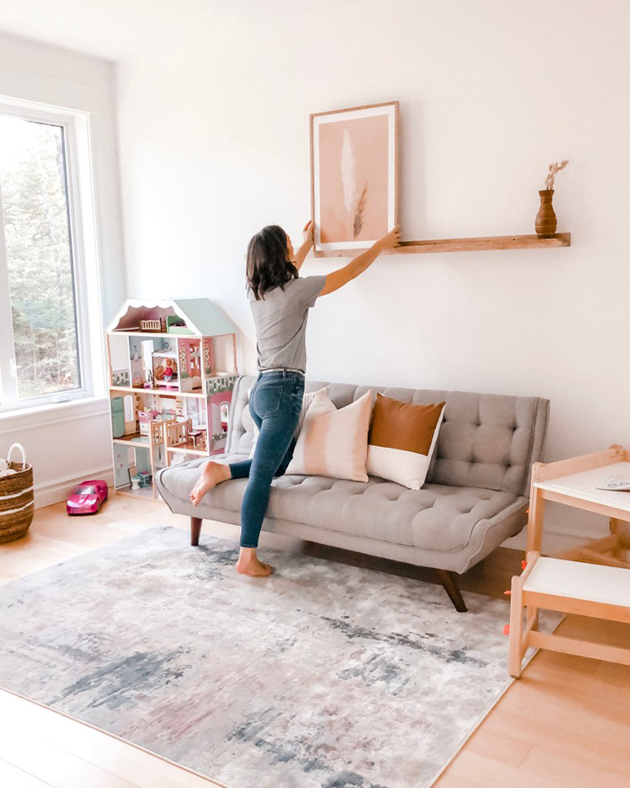 woman hanging a picture on a shelf living room design idea
