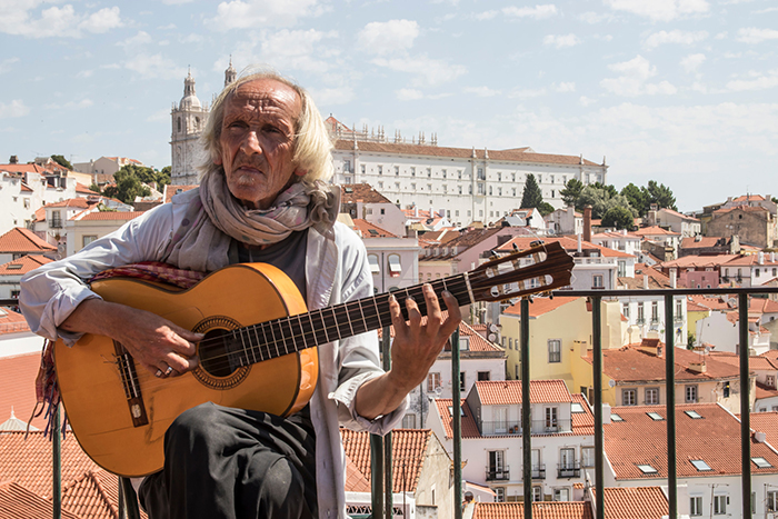 Old man with a guitar in Lisbon playing fado music Portuguese traditional music