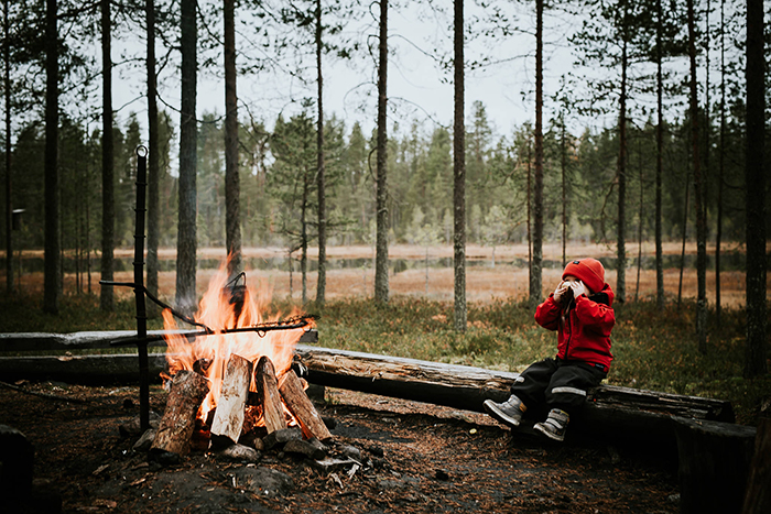 North Europe Nature of Finland child in red jacket around next to a fire forest