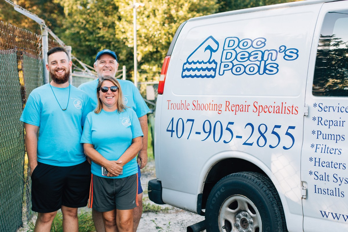 Family pool cleaning company members smiling in front of their professional bus