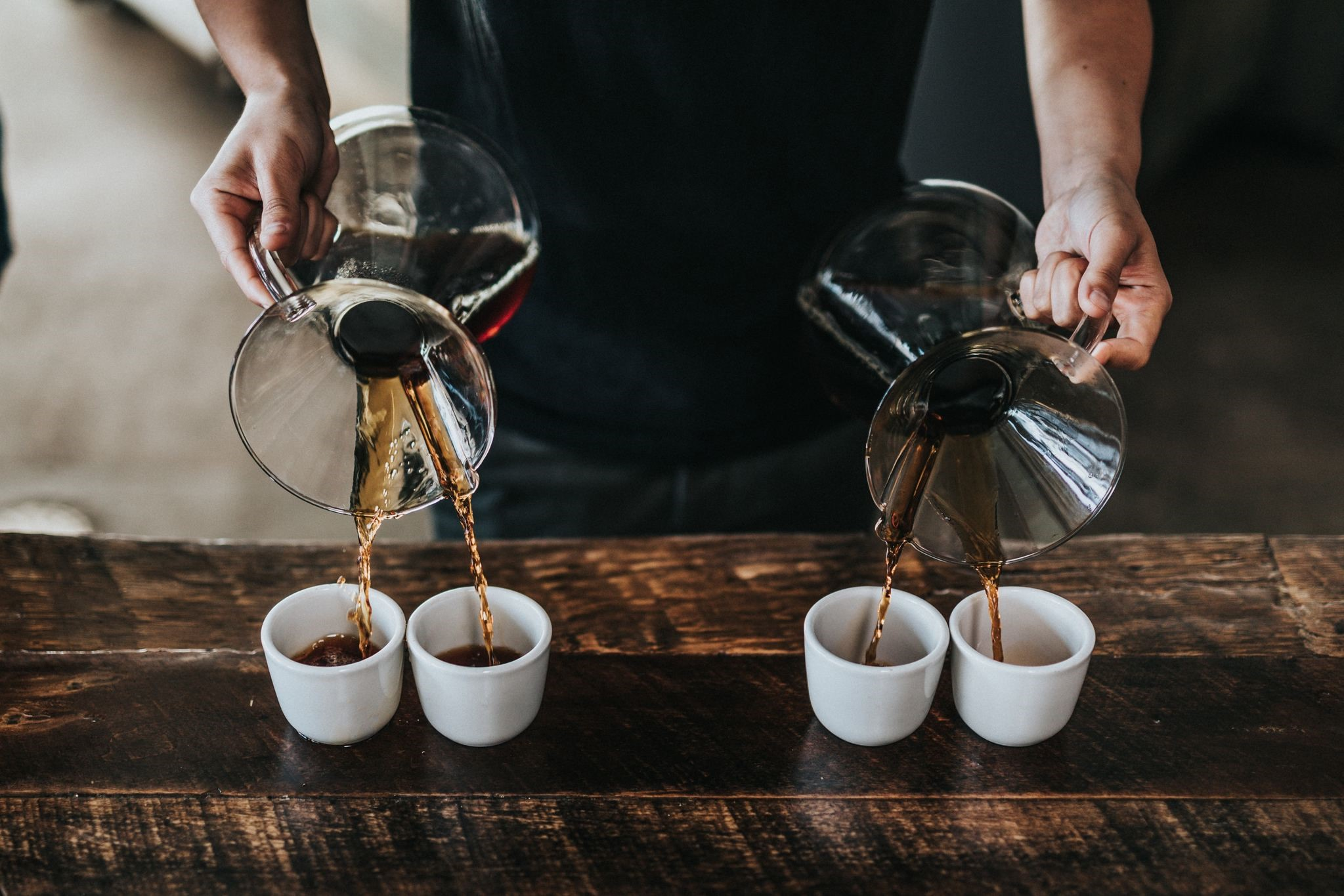 a man pours two-cup specialty coffee into four transparent coffee cups
