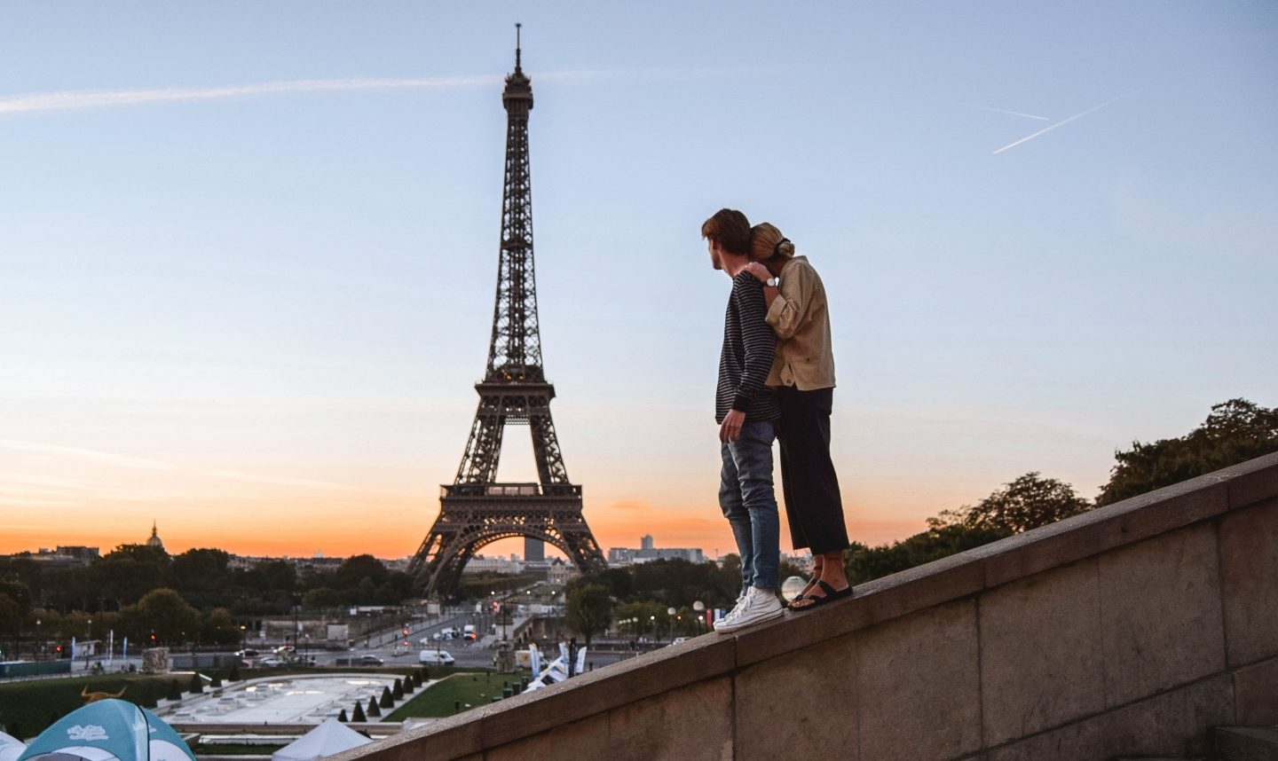 Things to do in Europe Paris couple looking at the Eiffel Tower Paris romance