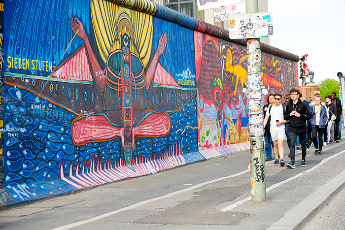 Things to do in Europe Berlin wall colorful wall people walking capital city