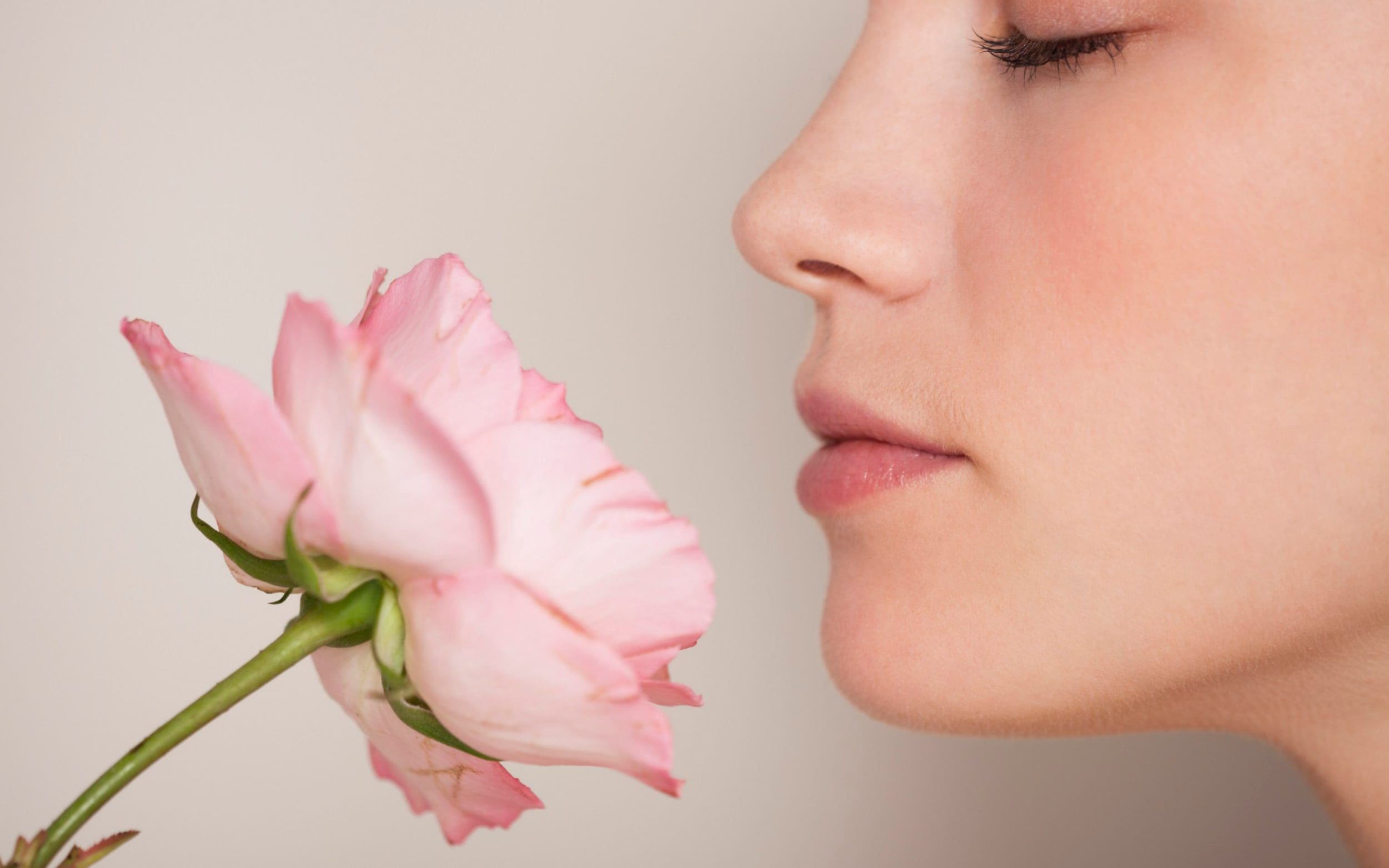 Woman with closed eyes smelling a bright pink rose