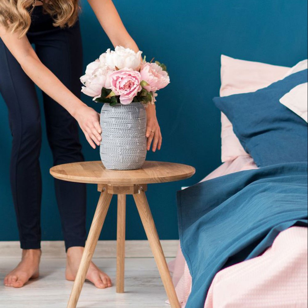 Woman decorating her bedroom with vase full of peony