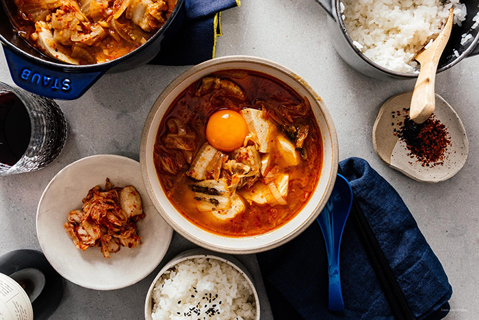 Korean soft tofu stew on a table with an egg rice bowls spices