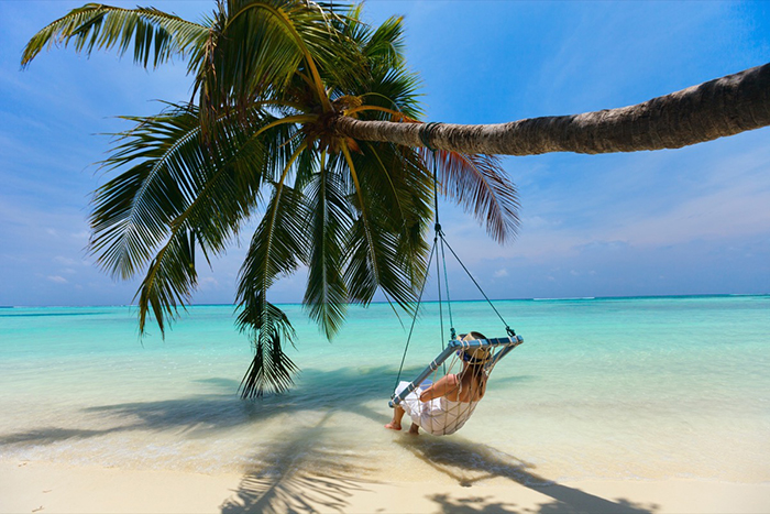 Exotic places woman in a hammock on a palm tree the Maldives clear blue water