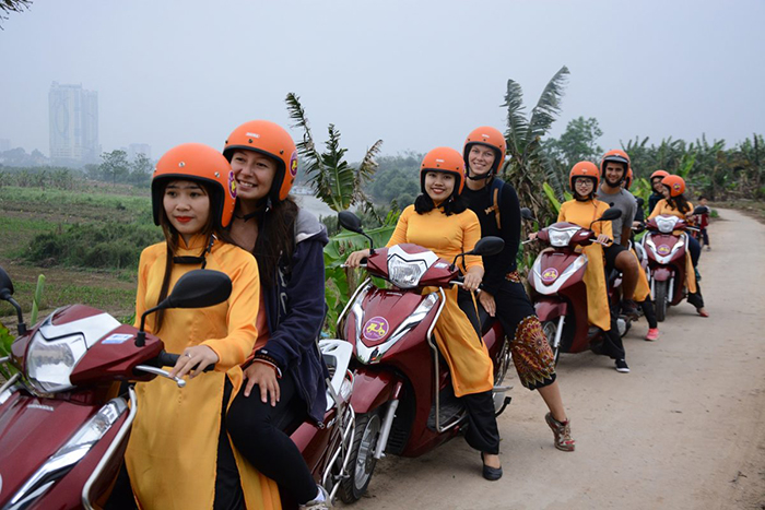 Girls on scooters tourists in Vietnam travel with friends