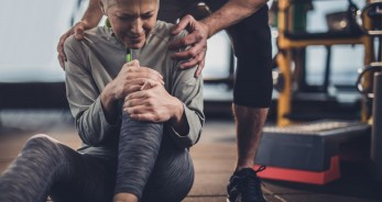 Woman at the gym with training clothes having pain in her leg
