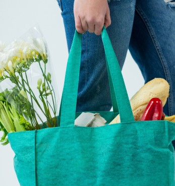 Woman with big textile bag full of vegetables, bread and flowers