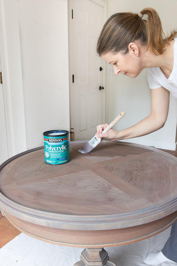 woman refinishing a table with paint and brush