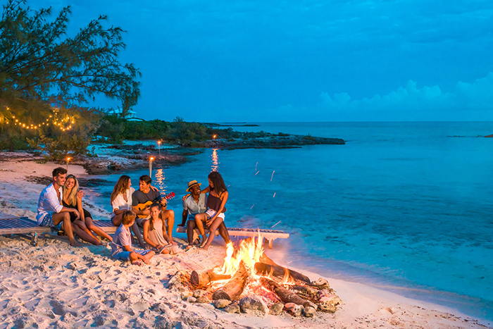 exotic places the bahamas friends around the fire couples playing the guitar