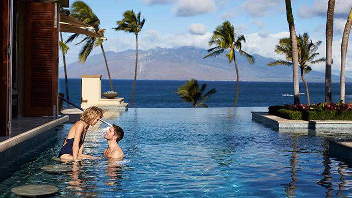 Top Hawaii Resorts Four Seasons Resort Maui outdoor infinity pool couple palm trees