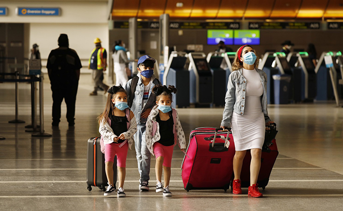 Vacation 2020 flying during coronavirus mother with three children wearing masks at the airport