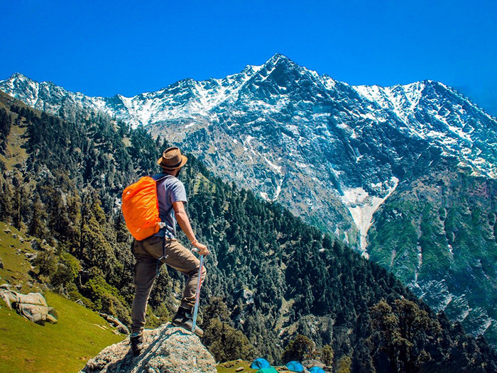 hiking during the summer a man with an orange backpack in the mountain looking at a peak covered with snow