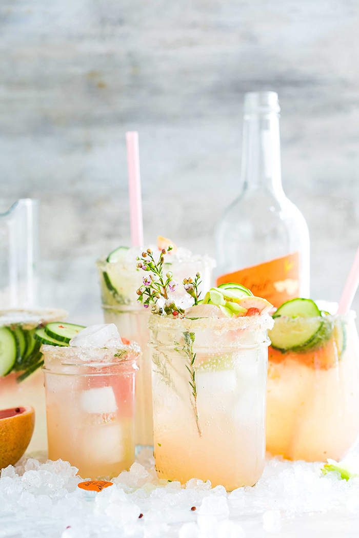 refreshing summer drinks a bottle and glasses with straws with vegetables herbs and ice