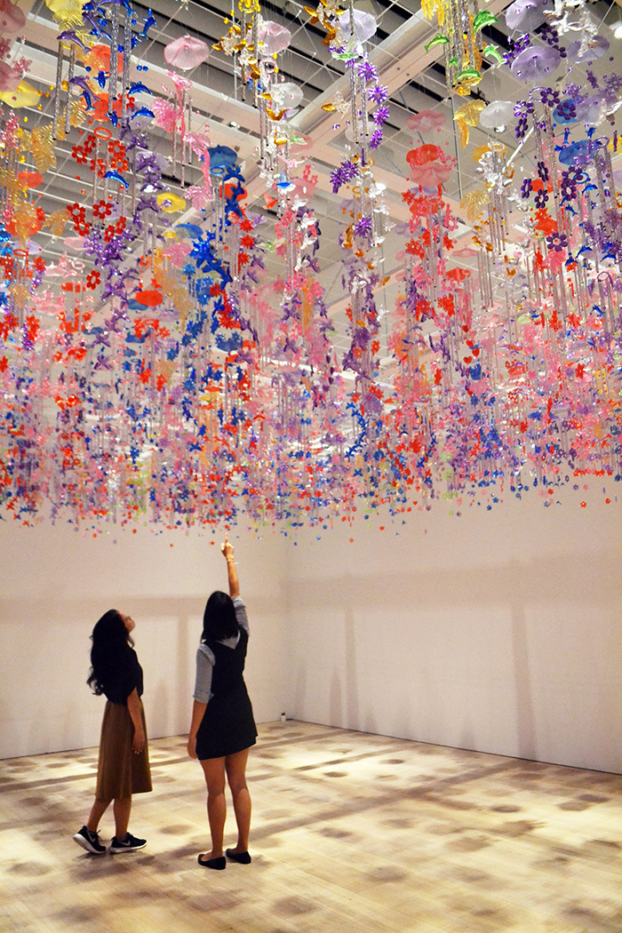 teamlab digital art exhibition two girls watching up in the mori art museum in a hall with flowers hanging from the ceiling