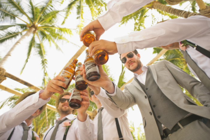 best bachelor party destinations men in suits cheering with bottles of beer with palms trees in the background