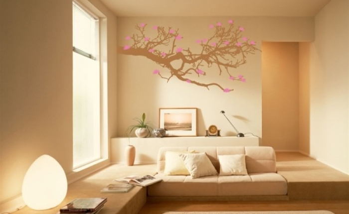 room in peachy color with beautiful tree branch with blossoming cherries simple living space