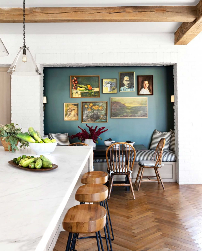 white stone wall in a cottage with contrasting blue wall and paintings kitchen island and wooden floor wooden roof beams