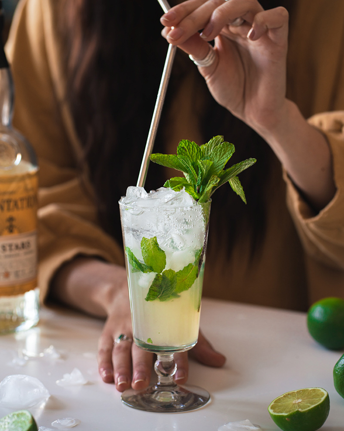 summer drinks ideas Mojito in a glass with ice and mint woman in the background holding a straw