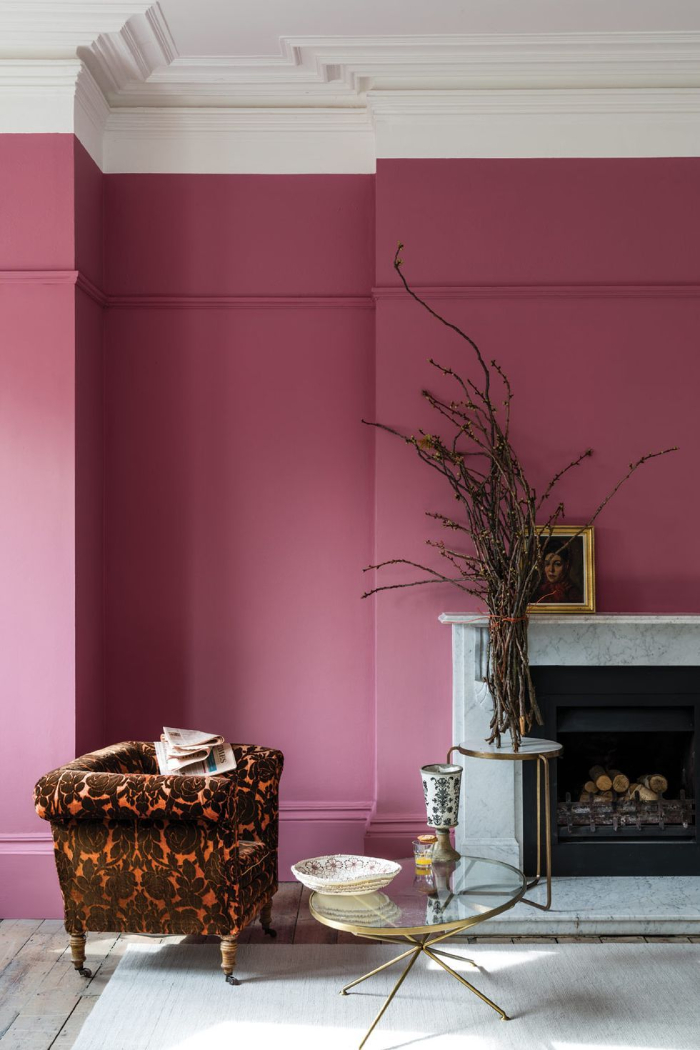 room in two different colors rich pink and white modern interior with classic fireplace colorful armchair and glass table