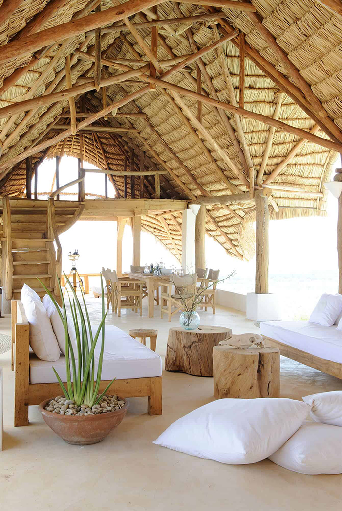 Rustic summer house with high rattan ceiling white and wooden furniture coastal style
