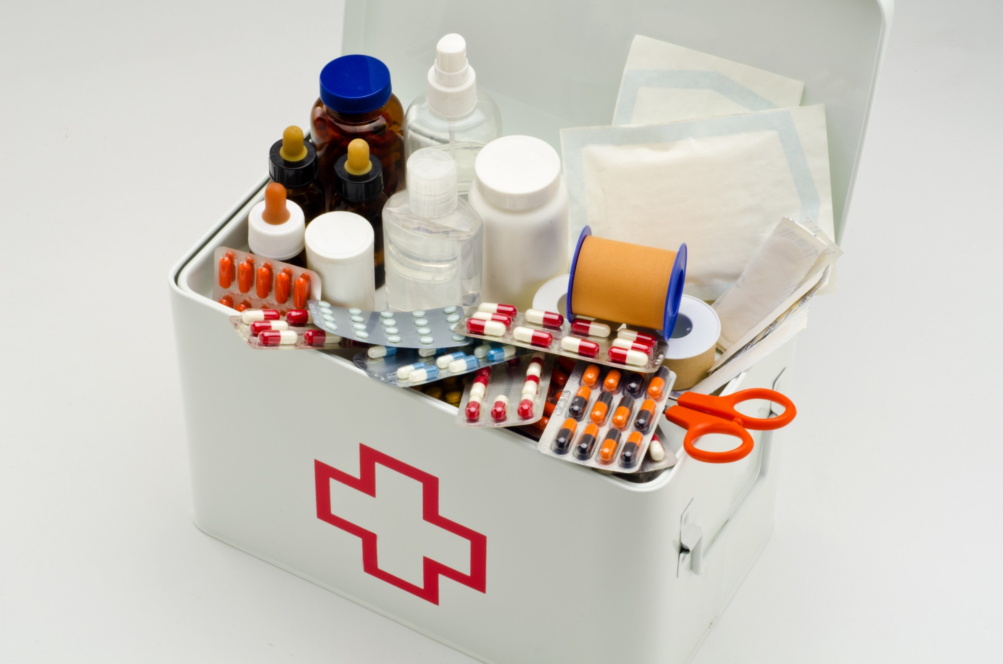 Open first aid box filled with medical supplies in white background