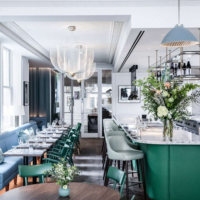allbright club london bar interior in green and white with fresh flowers and elegant chandeliers